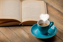 Tasse de café avec la vapeur de forme de coeur et le livre ouvert Image libre de droits