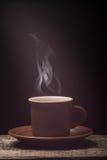 Tasse de café avec la vapeur sur le conseil en bois Fond noir Image stock