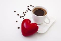 Tasse de café avec la vue à angles de grains de café de coeur et vers la gauche Photographie stock