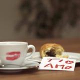 Tasse de café avec le baiser, le croissant et la note de rouge à lèvres Photographie stock libre de droits