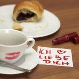 Tasse de café avec le baiser, le croissant et la note de rouge à lèvres Photographie stock