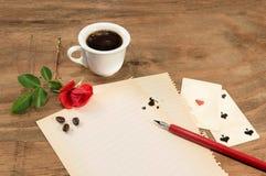 Tasse de café avec le bouton de rose rouge et de stylo sur le livre blanc Image libre de droits