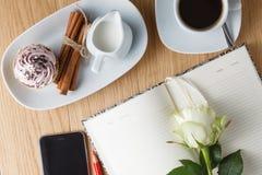 Tasse de café avec le carnet et le téléphone portable Images stock