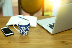 Tasse de café avec le carnet et le téléphone portable d'ordinateur avec la lumière du soleil Image libre de droits