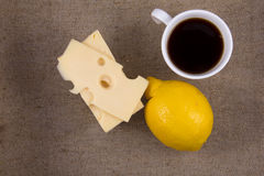 Tasse de café avec le citron et le fromage sur la toile de jute Images libres de droits