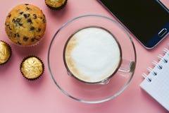 Tasse de café avec le dessert et le téléphone sur une table Images stock