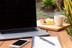 Tasse de café avec le fruit frais et l'ordinateur portable sur la table en bois dans le jardin images libres de droits