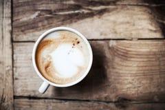 Tasse de café avec le modèle de coeur dans une tasse blanche sur le fond en bois Photo stock