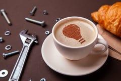 Tasse de café avec le symbole d'idée d'une ampoule sur la mousse Le café donne de nouvelles idées et créativité Pause-café de mat images stock
