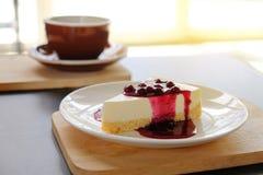 tasse de café avec le tarte de fromage de myrtille du plat en bois Images stock