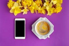 Tasse de café avec les fleurs de narcisse et le téléphone intelligent Image libre de droits