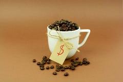 Tasse de café avec les grains de café et le symbole dollar d'arc Images stock