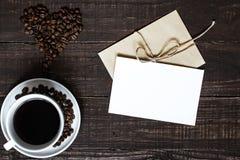 Tasse de café avec les haricots en forme de coeur et la carte de voeux blanche vierge Images libres de droits