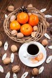 Tasse de café avec les mandarines et la noix photo stock