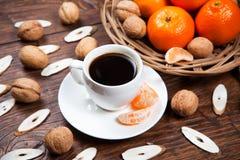 Tasse de café avec les mandarines et la noix Image stock