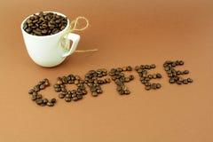Tasse de café avec un arc et un mot de grain de café Photo stock