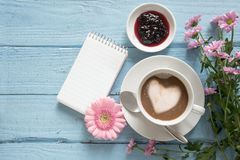 Tasse de café avec un coeur de mousse de lait, de fleurs roses et d'une écriture Image libre de droits