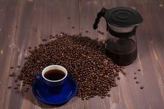 Tasse de café avec un fabricant de café et un groupe de grains de café dessus Photographie stock libre de droits