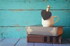 Tasse de café avec un peu de tableau de forme de coeur et à la pile de vieux livres Photographie stock