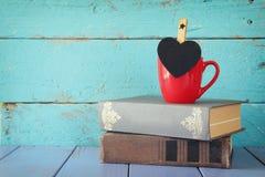 Tasse de café avec un peu de tableau de forme de coeur et à la pile de vieux livres Photo libre de droits