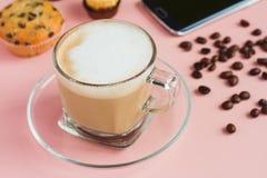 Tasse de café avec un téléphone et des haricots sur une table rose Images libres de droits