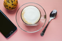 Tasse de café avec un téléphone sur une table rose Photographie stock libre de droits