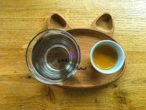 Tasse de café avec un verre de l'eau sur un plateau photographie stock libre de droits
