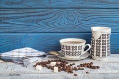 Tasse de café, beens et une cruche sur un fond des conseils bleus Photos stock