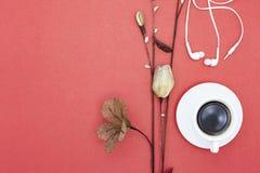 Tasse de café blanc avec la fleur de papier et l'écouteur sur le CCB rouge de papier Images libres de droits