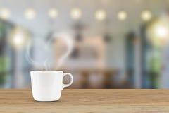 Tasse de café blanc avec de la fumée en forme de coeur sur le fond brouillé de café Images libres de droits