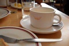 Tasse de café blanc avec la marque de rouge à lèvres sur le Tableau I de petit déjeuner Image libre de droits