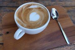 Tasse de café blanc chaude avec l'art de latte de forme de coeur Photographie stock