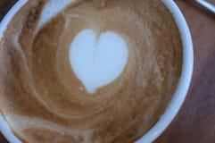 Tasse de café blanc chaude avec l'art de latte de forme de coeur Image stock
