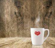 Tasse de café blanc chaude avec le coeur rouge sur le bois en bois de plancher et de tache floue Image libre de droits