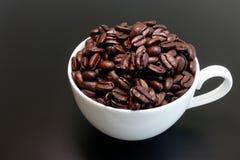 Tasse de café blanc complètement de grains de café frais Photos stock
