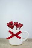 Tasse de café blanc décorée du coeur et du ruban rouges de scintillement pour Photos libres de droits