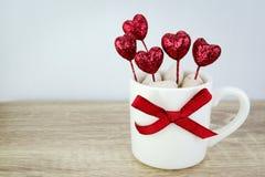 Tasse de café blanc décorée du coeur et du ruban rouges de scintillement pour Images stock