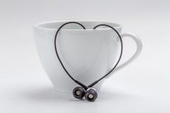 Tasse de café blanc et coeur-forme des écouteurs noirs sur le Ba blanc Photos stock