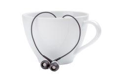 Tasse de café blanc et coeur-forme des écouteurs noirs sur le Ba blanc Photographie stock