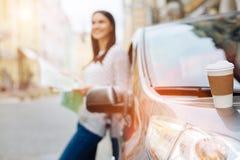 Tasse de café blanc se tenant sur le capot de voiture Images libres de droits