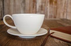 Tasse de café blanc sur un bureau et un book1 en bois Image libre de droits