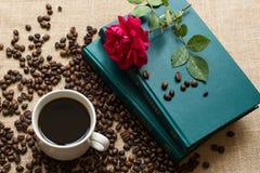 Tasse de café blanche, avec des grains de café sur le fond de livres Photos stock