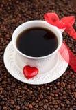 Tasse de café blanche avec le coeur rouge sur des grains de café Photos stock