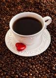Tasse de café blanche avec le coeur rouge sur des grains de café Photographie stock libre de droits