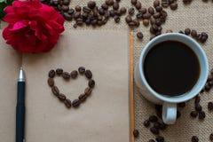 Tasse de café blanche, avec les grains de café et le carnet à dessins Images libres de droits