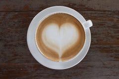 Tasse de café blanche chaude avec la forme de coeur sur la table en bois de la vue supérieure Photo stock
