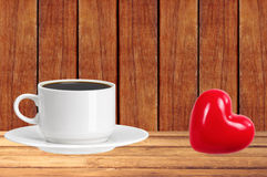 Tasse de café blanche sur la table en bois avec le coeur rouge Photos libres de droits