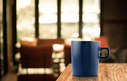 Tasse de café bleu-foncé sur la table en bois à l'arrière-plan de café de tache floue Image stock