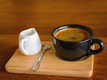 Tasse de café bleue de noir foncé avec du café d'americano, la cuillère et un MI Images libres de droits