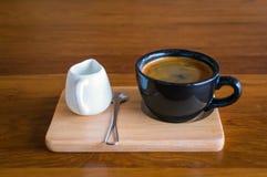 Tasse de café bleue de noir foncé avec du café d'americano, la cuillère et une cruche de lait sur un support en bois Photo libre de droits
